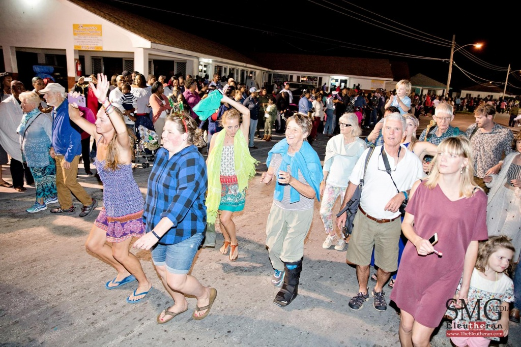 Onlookers joining in the festive dance to the steady beats of Cultural Bahamas Junkanoo in Eleuthera