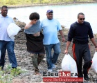 Royal Bahamas Police Force in Eleuthera, escorts the suspect and bags of items from his hiding spot.