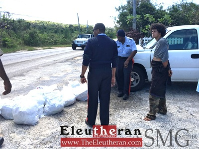 The suspect is pictured with police and bags of recovered items in Governor's Harbour, on Friday morning.
