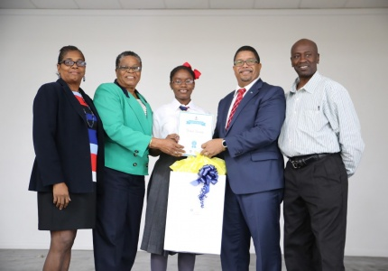 """OUTSTANDING JOB – Deputy Prime Minister and Minister of Finance, the Hon. K. Peter Turnquest (second from right) presents Yana Swain of Mary, Star of the Sea Catholic School, with her certificate and award for winning the essay competition hosted by the Caribbean Organization of Tax Administrators. Under the theme, """"Reformation of Taxes"""" the essay competition was held in June of this year and Yana won over all of the entrants from The Bahamas. Also on hand for the presentation, which took place on Monday, October 30, 2017 at Mary Star, were Rosemary Pintard-Bowe, Acting Comptroller for the Department of Inland Revenue (second from left); Vice Principal of Mary Star, Mrs. Hanna (left) and Yana's dad, Denzel Swain (right).  (BIS Photo/Lisa Davis)"""