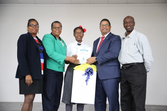 "OUTSTANDING JOB – Deputy Prime Minister and Minister of Finance, the Hon. K. Peter Turnquest (second from right) presents Yana Swain of Mary, Star of the Sea Catholic School, with her certificate and award for winning the essay competition hosted by the Caribbean Organization of Tax Administrators. Under the theme, ""Reformation of Taxes"" the essay competition was held in June of this year and Yana won over all of the entrants from The Bahamas. Also on hand for the presentation, which took place on Monday, October 30, 2017 at Mary Star, were Rosemary Pintard-Bowe, Acting Comptroller for the Department of Inland Revenue (second from left); Vice Principal of Mary Star, Mrs. Hanna (left) and Yana's dad, Denzel Swain (right). (BIS Photo/Lisa Davis)"