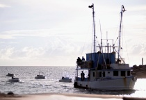 One of the apprehended vessels with skiffs in tow entering the Coral Harbour Base.