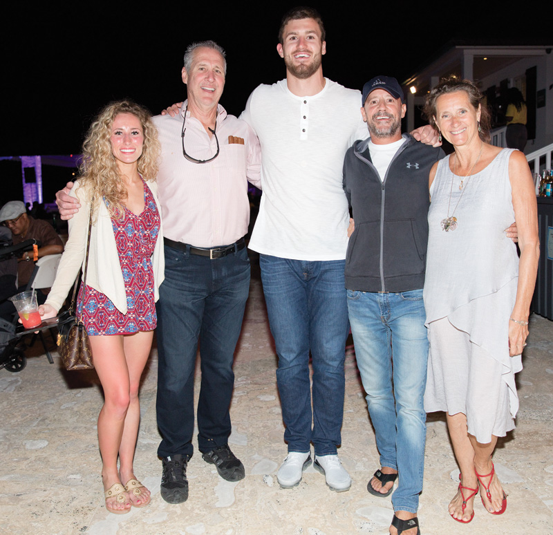 Professional football player, Jesse James (center) with friends, along with girlfriend, Alex Lauth (left) next to her father, Eddie Lauth at French Leave's Jazz Fest event.