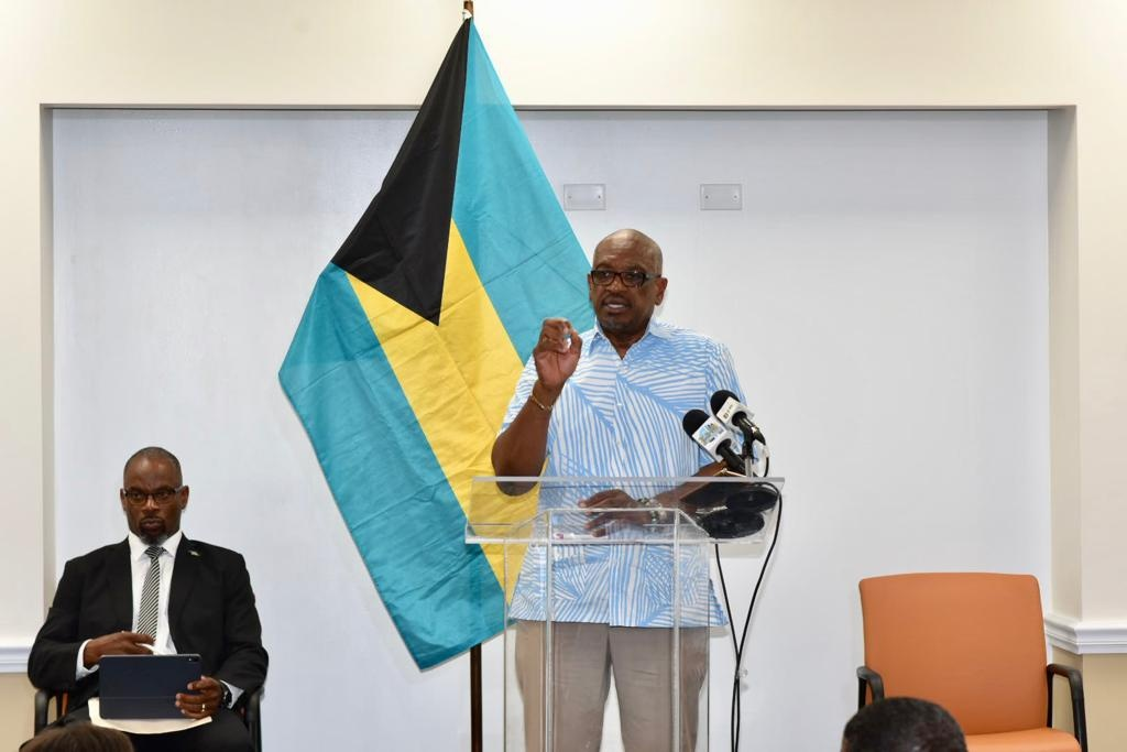 Prime Minister Minnis (at podium), with Mr. Iram Lewis shown on left.