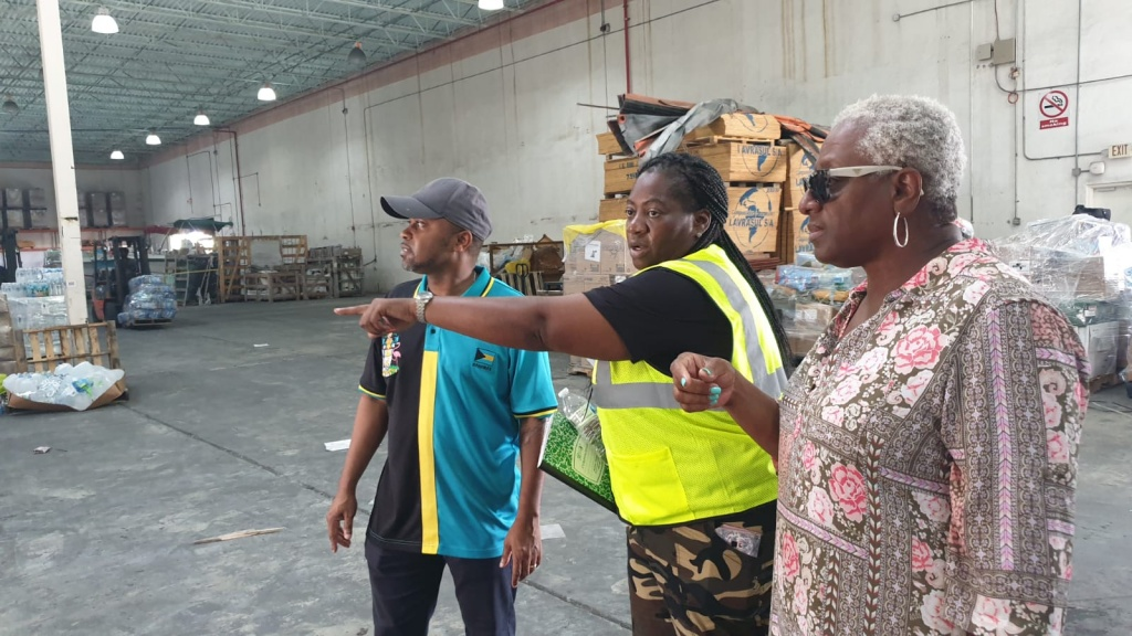 "Minister of State for Grand Bahama, Senator Kwasi Thompson (left) and President of the Senate and NEMA coordinator, Kay Forbes-Smith (right), listens as Tammy Mitchell from the National Emergency Management Agency (NEMA) explains what supplies recently arrived in Grand Bahama at the Freeport Ship Services Warehouse, on Saturday, September 14, 2019. Saturday was the launch of ""Operation Relief Saturday,"" where hurricane relief supplies were taken directly to the door of residents in need."