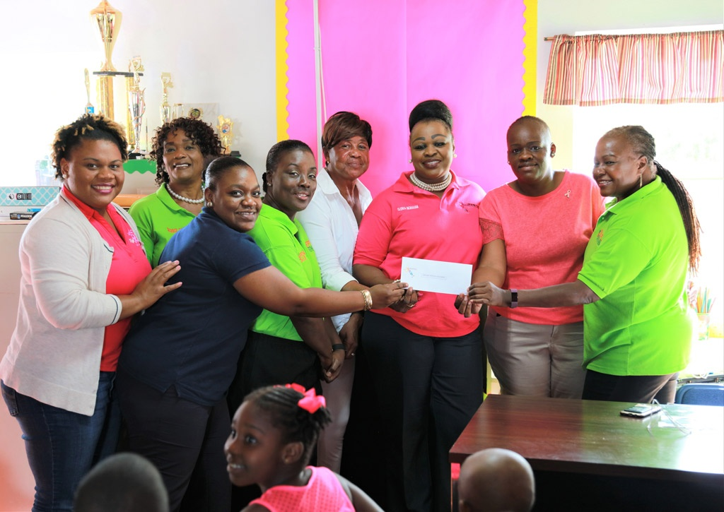 Pineapple Fest Chairwoman and Ministry of Tourism representatives make a check presentation to the Gregory Town primary school.