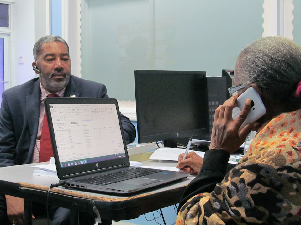 Former Deputy Director of Social Services, Ms. Marva Minns, works the phone lines while providing voluntary service at the Help Desk. Minister Campbell observes the process. (BIS Photo/Matt Maura)