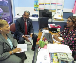 Mrs. Cheryl Carroll, Chief Probation Officer, Department of Rehabilitative Welfare Services (right), who heads the Help Desk, provides a progress report to Minister of Social Services and Urban Development, the Hon. Frankie A. Campbell, during a recent visit. Also pictured is: Mrs. Lilian Quant-Forbes, Director, Department of Social Services, Ministry of Social Services and Urban Development. (BIS Photo/Matt Maura)