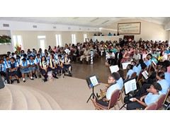 Expansive room of supportive family and friends with the school band at the front right and graduates on the left - 490A7612