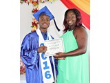 Valedictorian of the WHS Class of 2016, Naaman Rolle, receiving an award in Physical Education from teacher Ms. Campbell - 490A3283